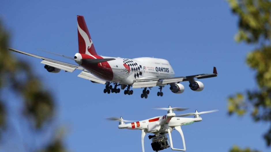 Drohne neben Flugzeug.