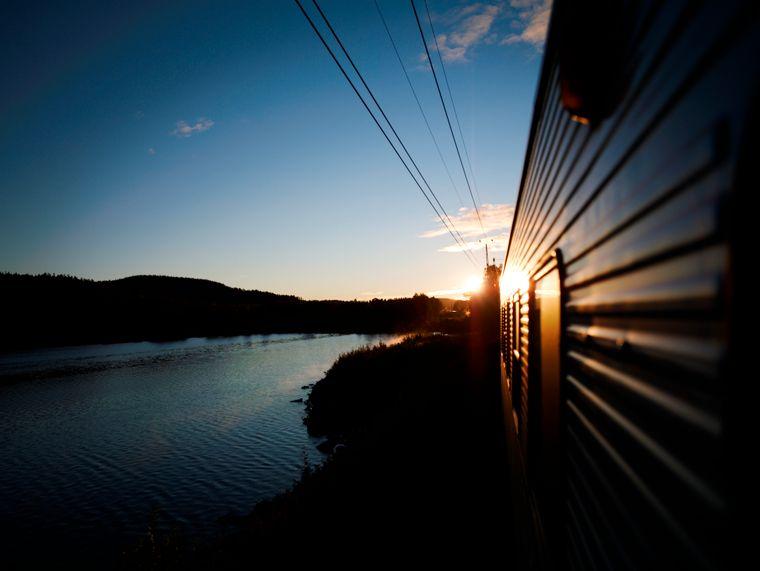 Ein Nachtzug fährt in Schweden in der Dämmerung an einem See entlang.