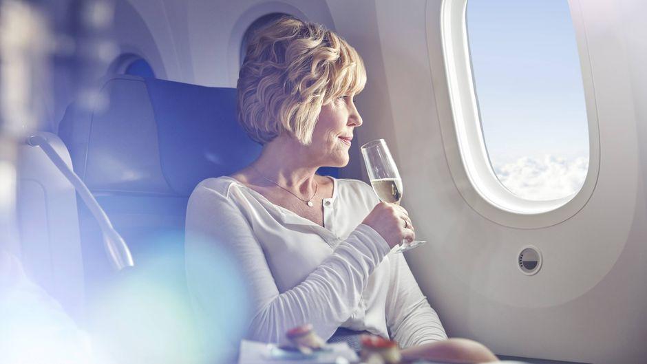 Frau trinkt Champagner in der First Class im Flugzeug.