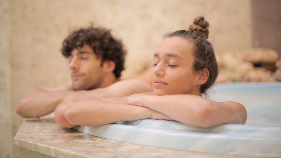 Zwei Menschen genießen ein Bad in einem Wellness-Bad.