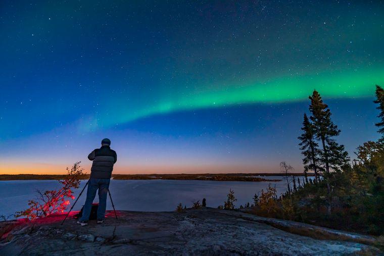 Fotograf vor Nordlichtern über dem Prelude Lake bei Yellowknife, Kanada.