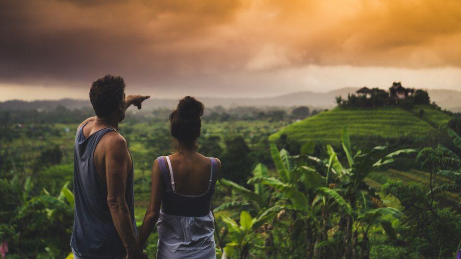 Ein Paar auf Bali: Der Mann zeigt in die Ferne.