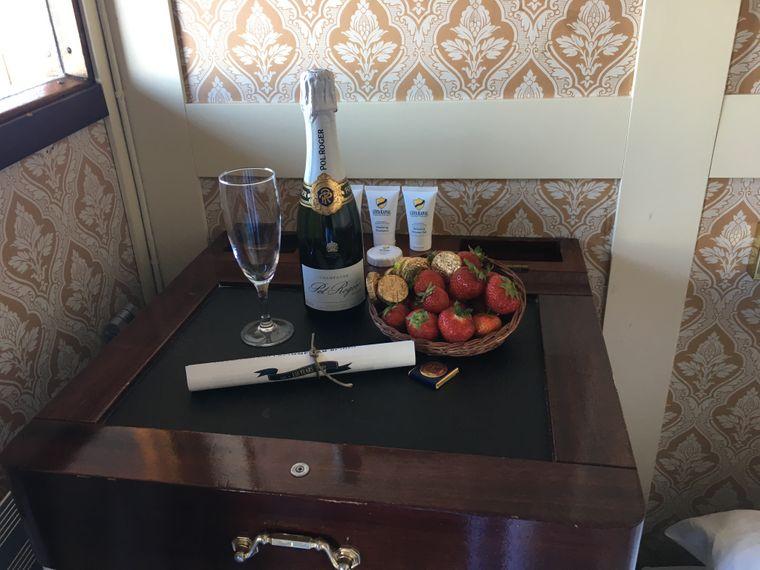 """Freundlicher Empfang: Auf dem Oberdeck gibt es zur Begrüßung Champagner und Obst. Der """"Tisch"""" ist übrigens der Deckel über dem Waschbecken."""