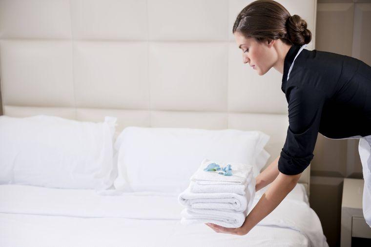 Zimmermädchen bringt einen Stapel Handtücher in ein Hotelzimmer.