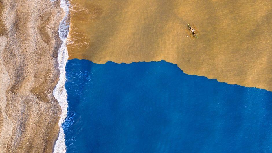 Schlammiger Fluss trifft auf klaren Ozean.