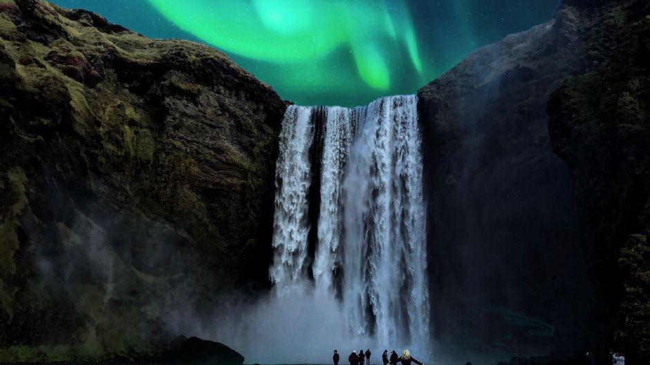 Vor besonders spektakulärer Kulisse schweben die grün-gelben Schleier auf Island, wie hier am Wasserfall Skógafoss.