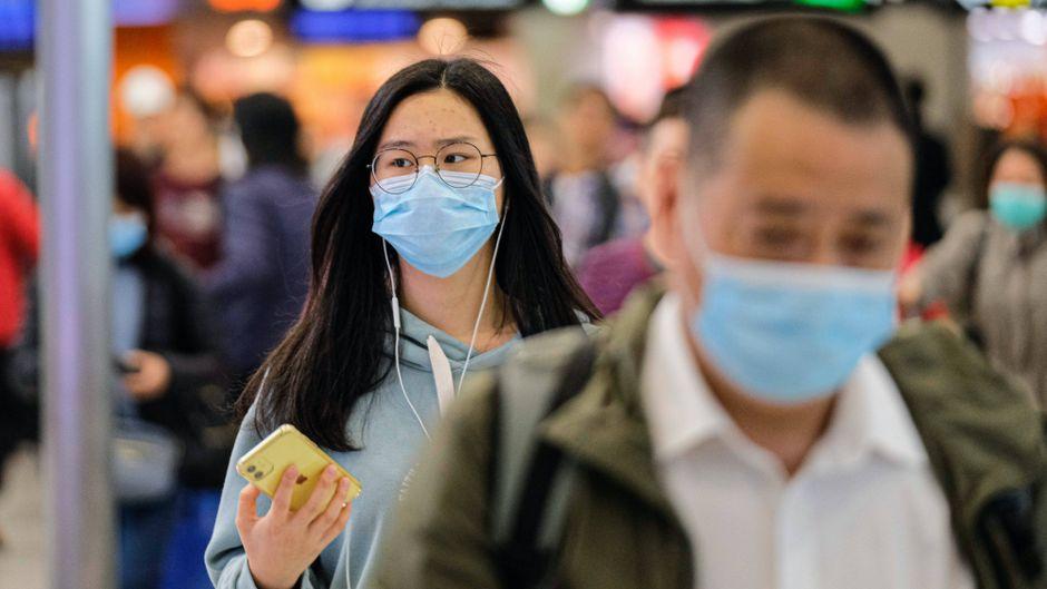 Menschen mit Atemmasken am Flughafen.
