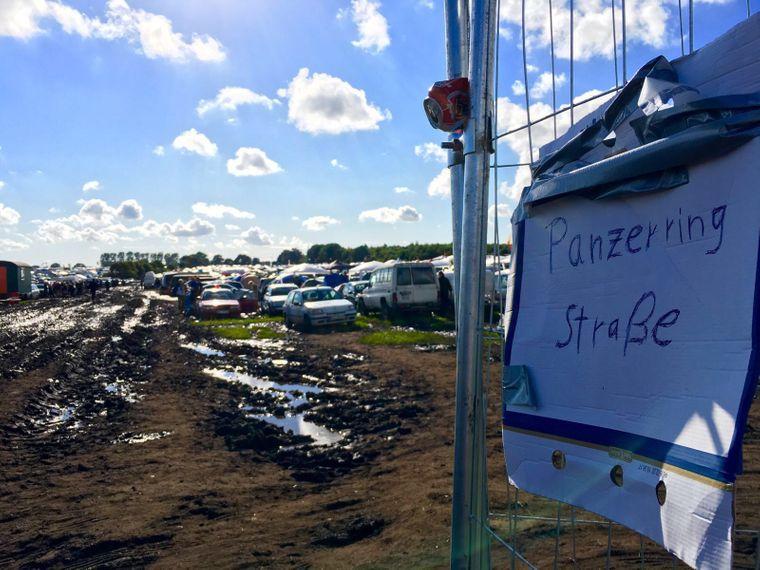 Blick auf einen Parkplatz mit selbst gebasteltem Schild beim Wacken Open Air 2016