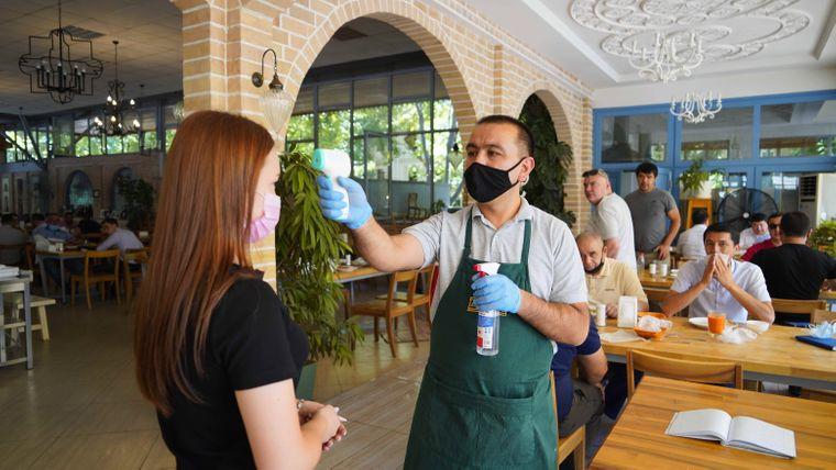 Ein Restaurant-Mitarbeiter überprüft die Temperatur eines Gastes in Tashkent, Usbekistan.