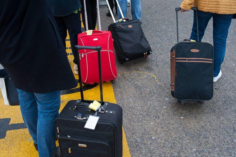 Passagiere ziehen ihre Handgepäckskoffer über das Rollfeld.