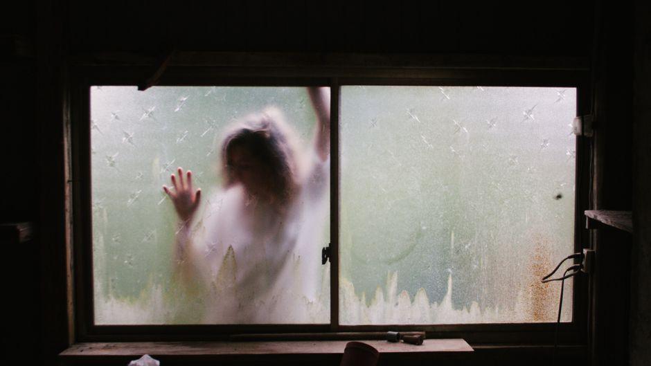 Eine Gestalt lehnt sich Hilfe suchend an eine Fensterscheibe.