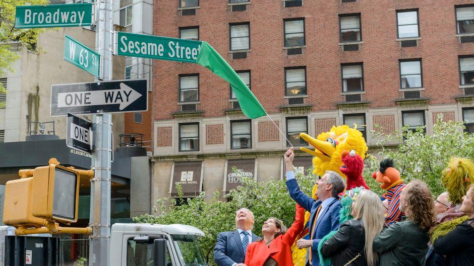 Bei der feierlichen Enthüllung des Straßenschilds waren natürlich auch die Sesamstraßen-Stars wie Ernie, Bibo und Elmo am Start.