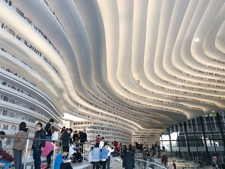 Weiße, wellenförmige Bücherregale führen versetzt an der Decke entlang.