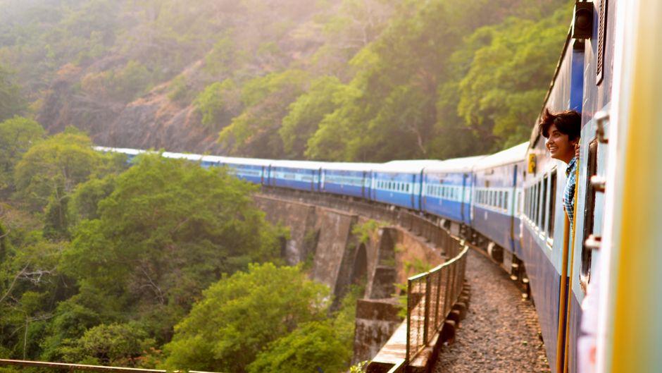 Junge schaut aus einem fahrenden Zug in Indien.