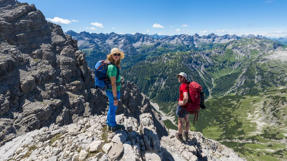 Zwei Wanderer schauen in die Kamera nach einer Wanderung durch die Alpen.