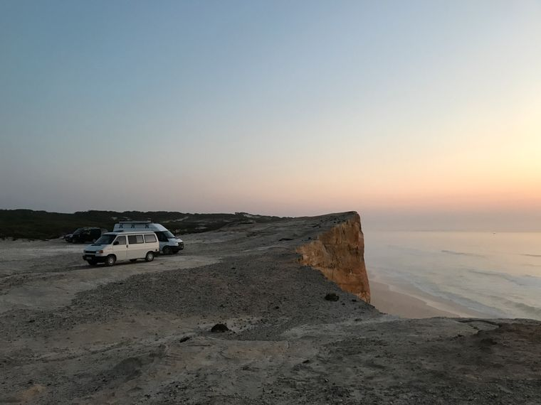 Vans stehen an einer Steilküste in Portugal bei Sonnenuntergang