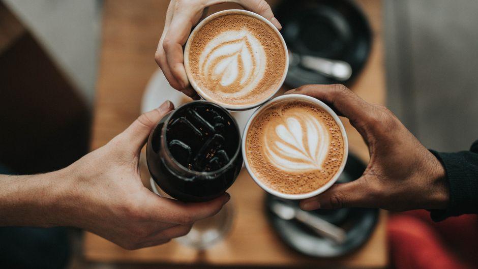 Menschen stoßen mit Kaffeegetränken an.