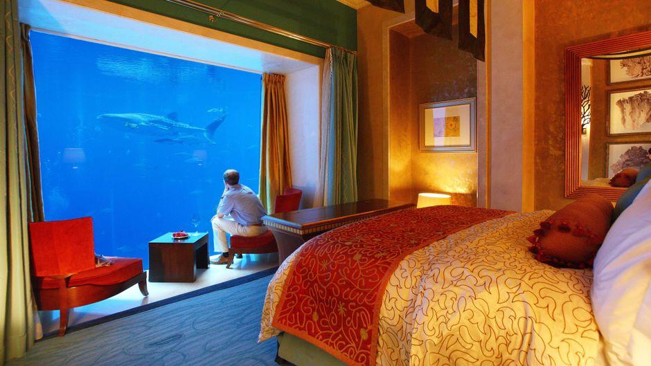 Ein Mann sitzt vor dem Panoramafenster im Schlafzimmer einer Unterwasser-Suite des Atlantis-Hotels in Dubai.