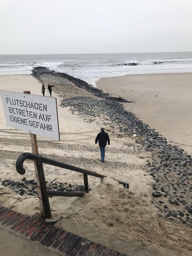 Warnschilder weisen auf die Schäden der Sturmflut am Strand hin.