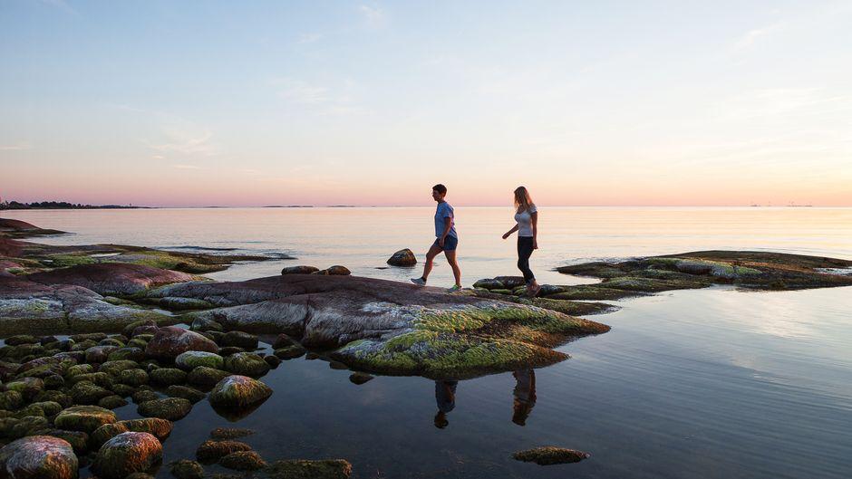 Zwei Frauen laufen im Sonnenuntergang über Felsen in Åland.