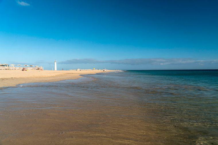 Die Playa del Matorral mit dem typischen Leuchtturm von Morro Jable auf Fuerteventura.