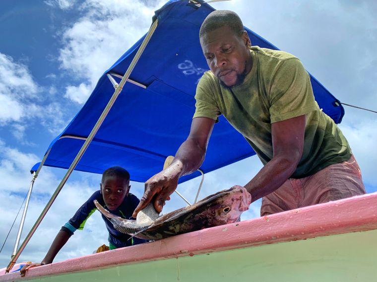 Kapitän Sean Barry und sein Sohn Kaeseon bereiten einen frisch gefangenen Fisch zum Grillen vor.