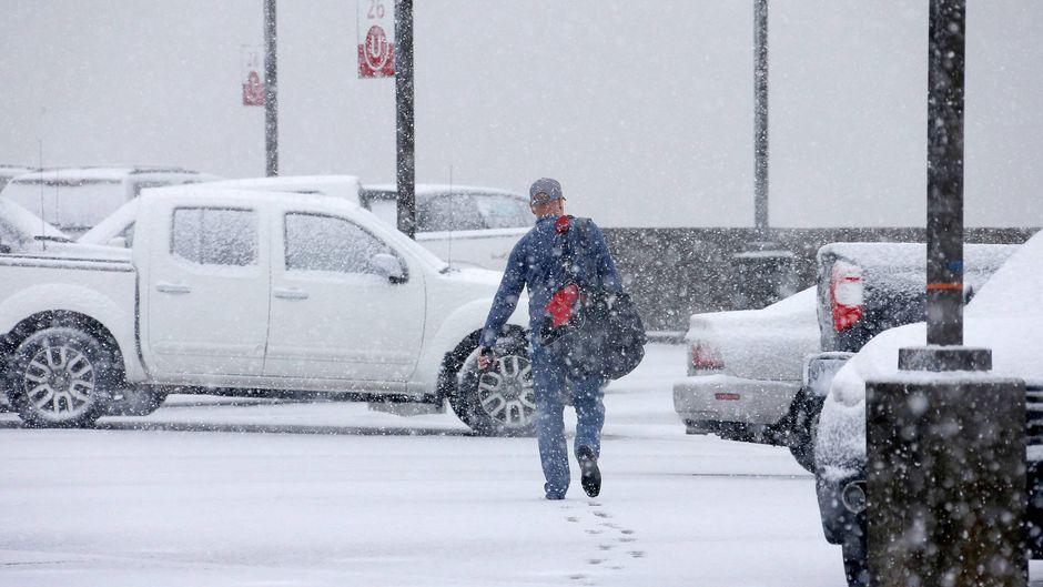 Mann stapft durch Schnee zu verschneiten Autos.