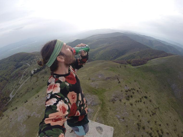Tyral trinkt ein Bier auf einem Berg.