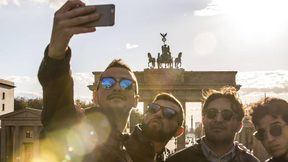 Touristen fotografieren sich vor dem Brandenburger Tor in Berlin.