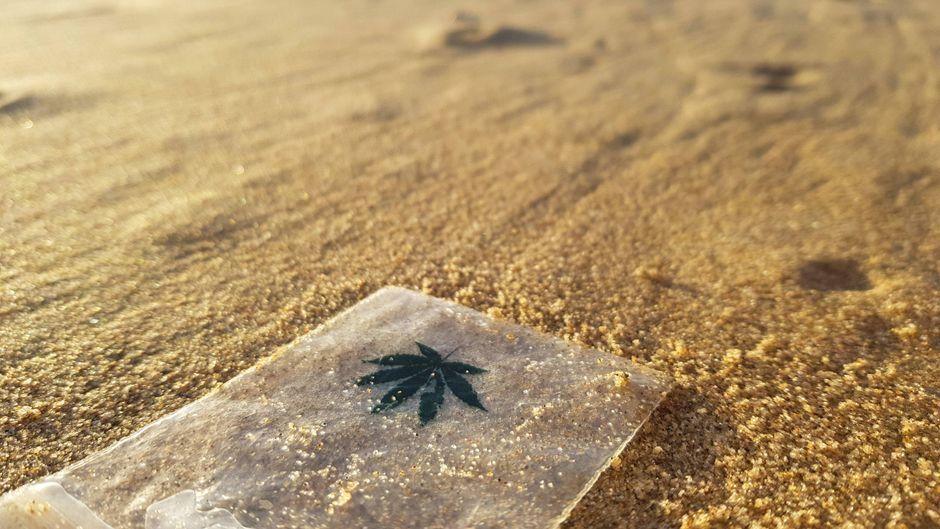 Ein Marihuana-Tütchen liegt leer an einem Strand.