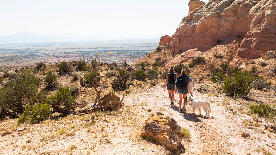 Eine Familie wandert durch eine Canyon-Landschaft in den USA.
