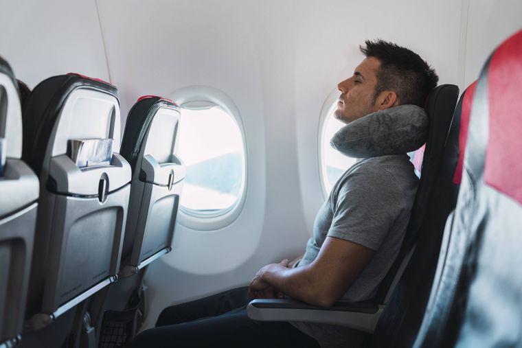 Mann schläft mit einem Nackenkissen im Flugzeug.