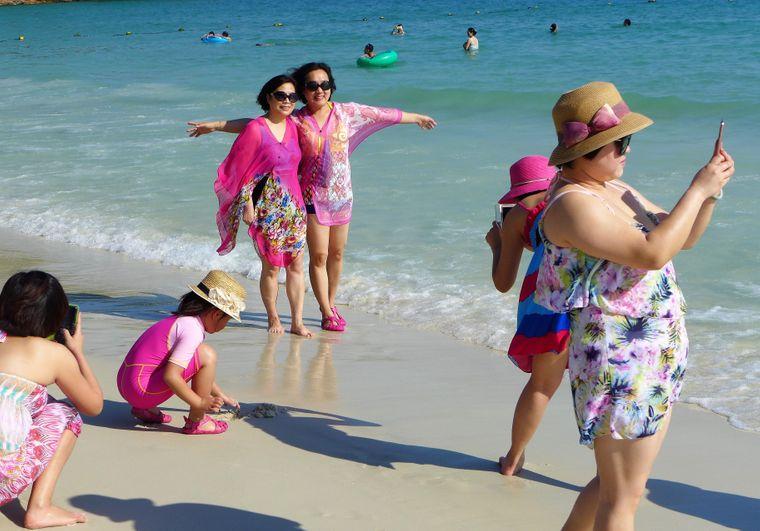 Urlauber schießen ein Urlaubsfoto am Strand von Koh Samet.