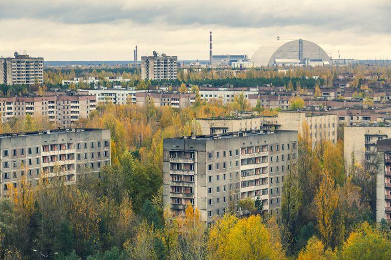 Im Vordergrund stehen die Wohnhäuser Prypjats, im Hintergrund ist das stillgelegte Kernkraftwerk Tschernobyl zu erkennen.