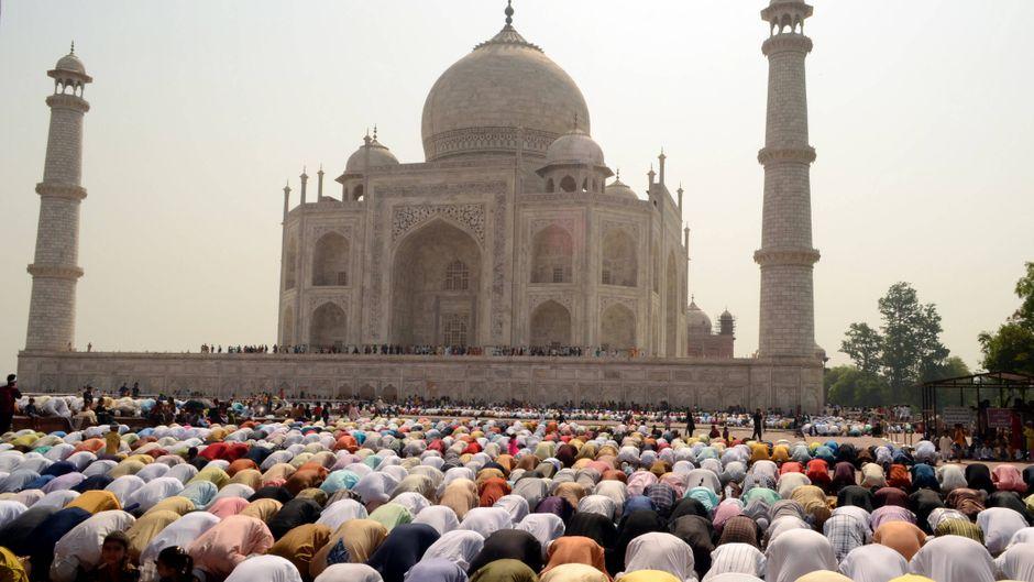Menschen beten vor dem Taj Mahal.