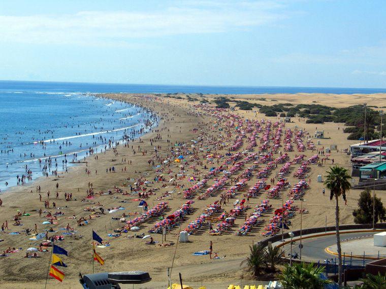 Die Playa de Inglés auf Gran Canaria am Meer mit Blick auf die Dünen von Maspalomas.