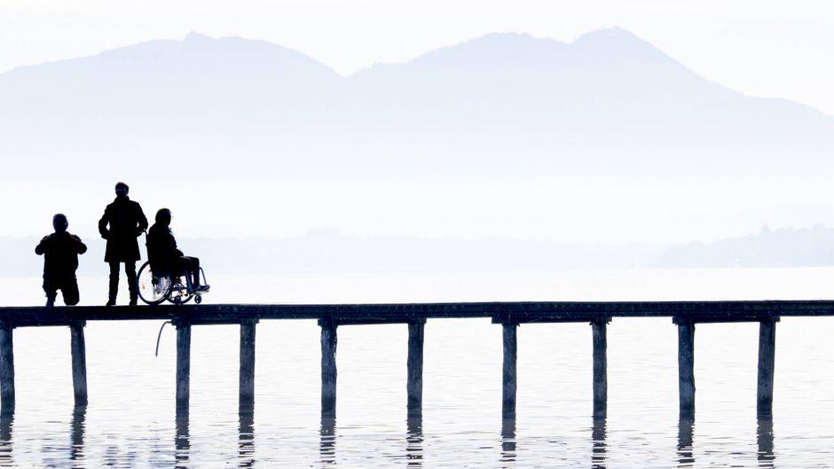 Silhouetten von drei Personen auf einem Steg am Chiemsee