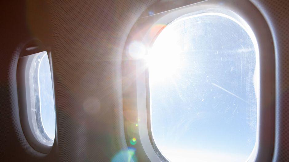 Die Sonne scheint durch zwei Flugzeugfenster.