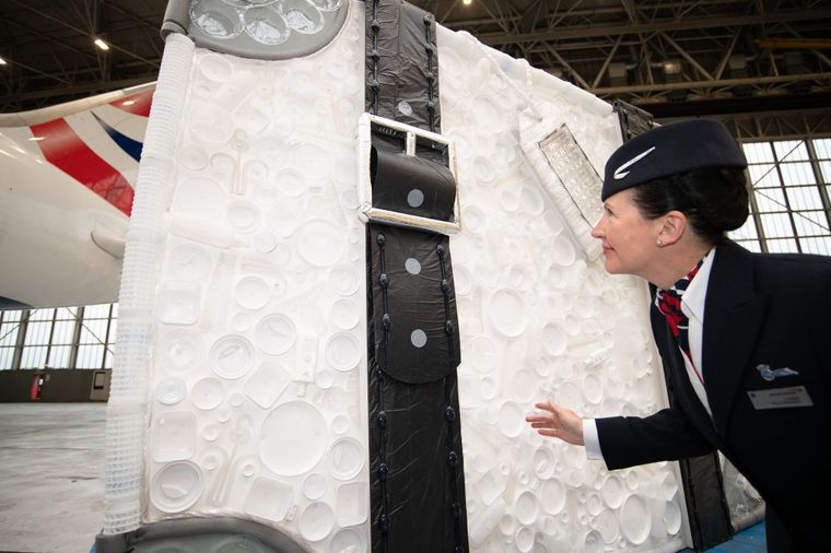 Stewardess vor riesengroßem Plastik-Koffer.