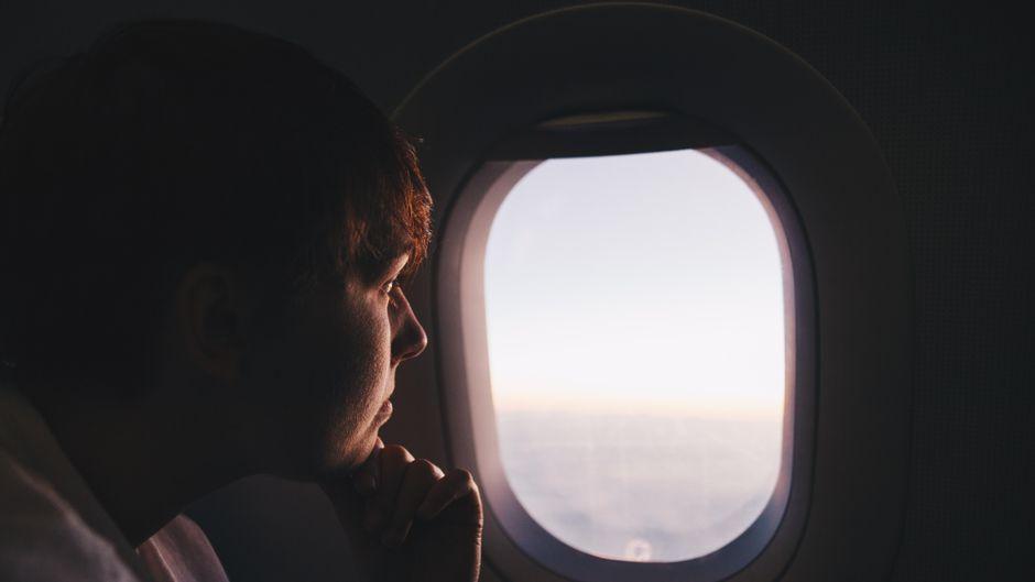 Ein Mann schaut aus dem Flugzeugfenster.