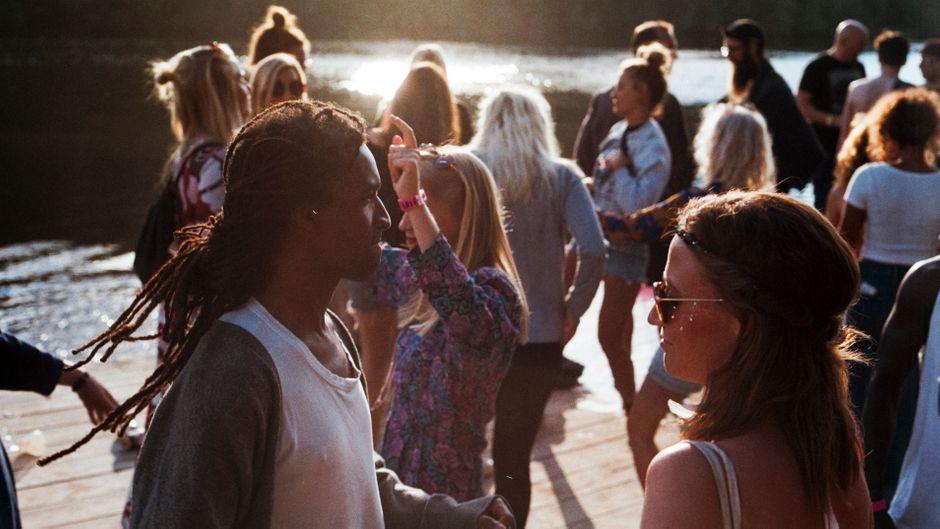 Menschen tanzen an einem Fluss in Schweden.