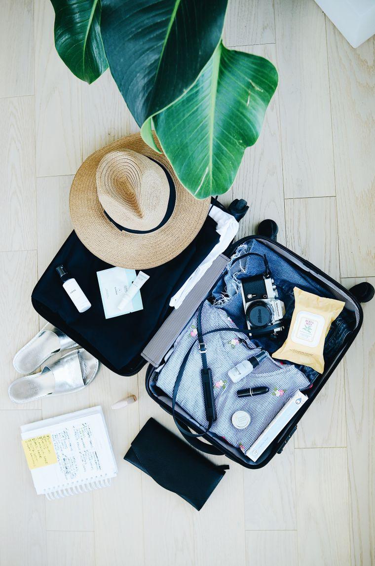 Handgepäckkoffer mit Klamotten, Kamera und Strohhut.