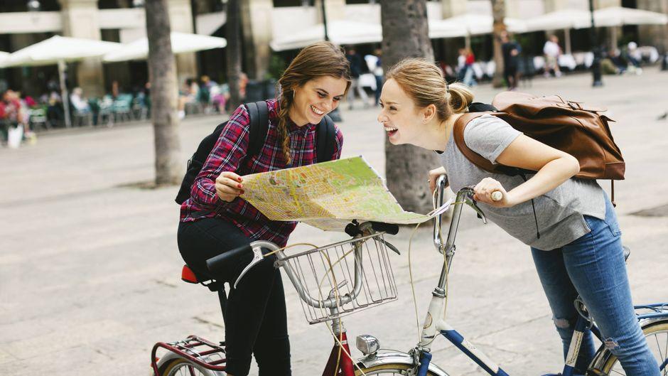 Zwei junge Frauen mit einem Stadtplan in Barcelona