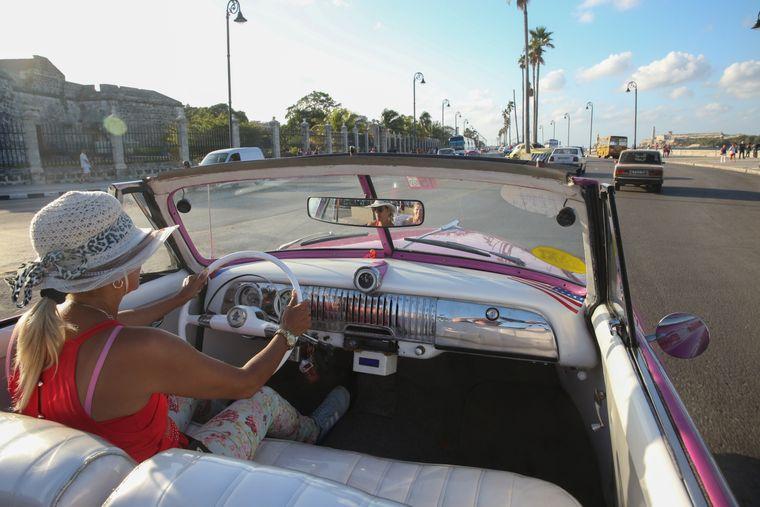 Frau fährt mit Oldtimer durch Havanna auf Kuba.