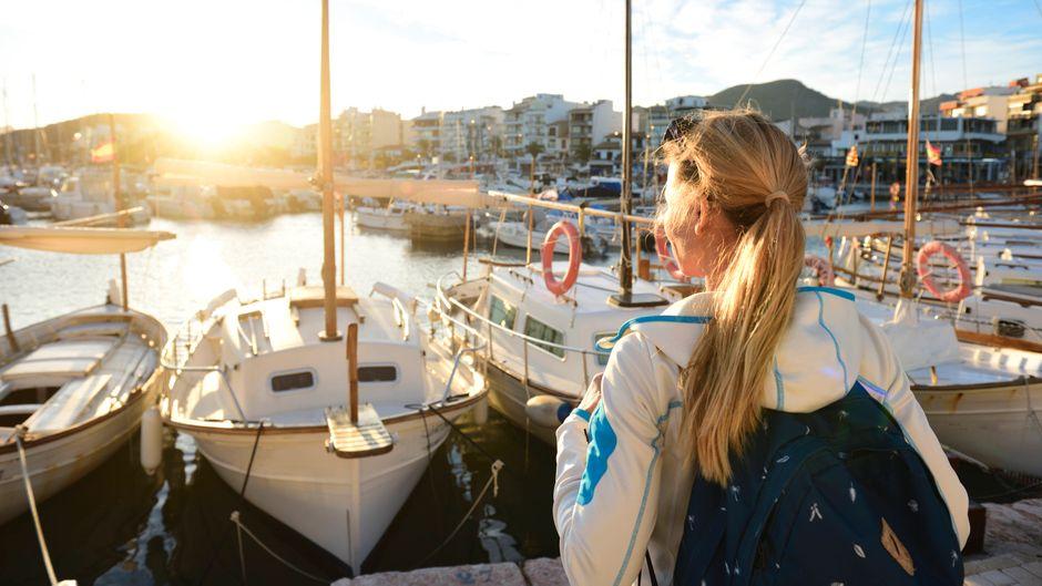 Eine Frau schaut auf den Port de Pollenca auf Mallorca. Urlauber können Flug-Tickets für den Testbetrieb ab Mitte Juni kaufen.
