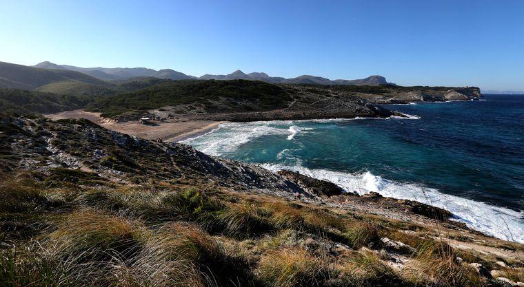Märchenhaft: Unter blauem Himmel branden die Wellen sacht am menschenleeren Sandstrand in der Cala Torta.