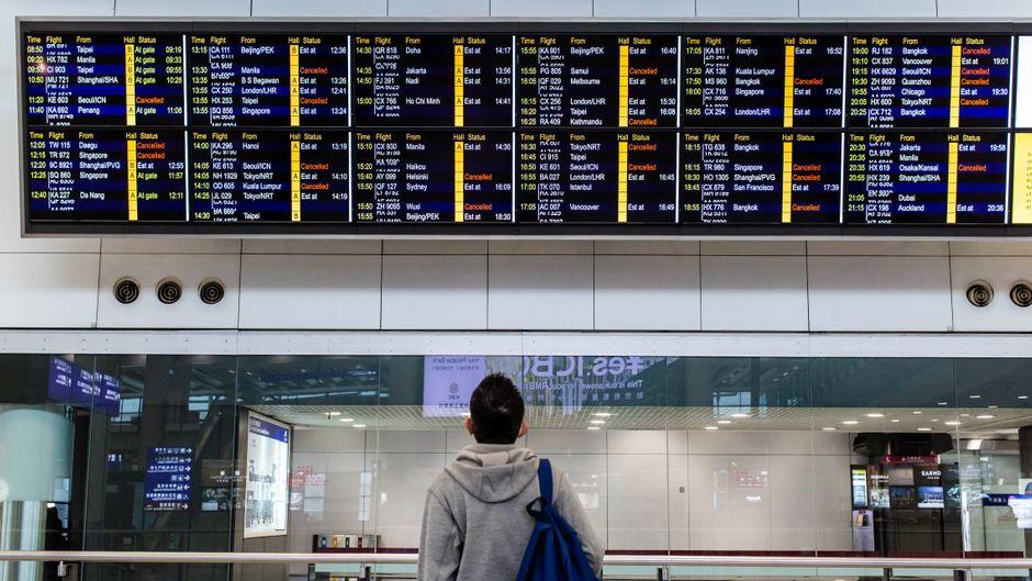 Ein Passagier studiert die Anzeigetafel am Flughafen in Hongkong.