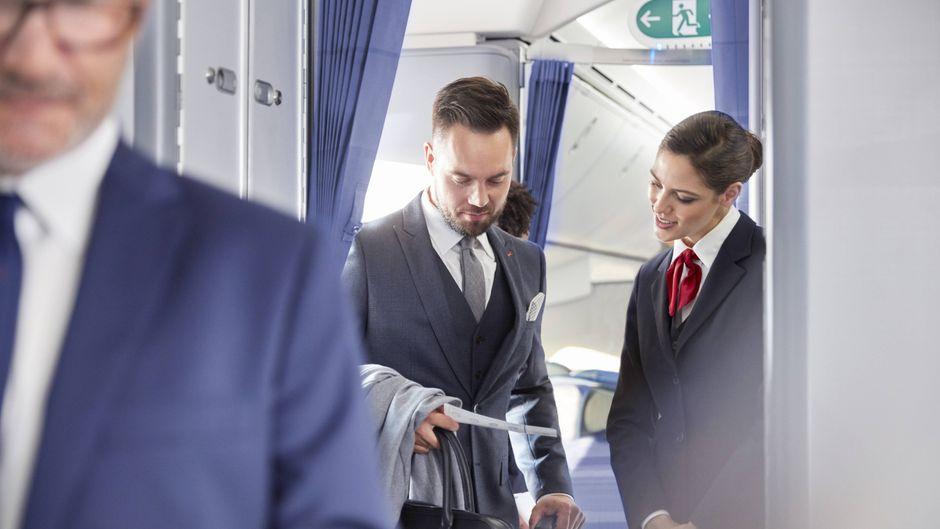 Flugbegleiterin hilft Passagier beim Boarding.