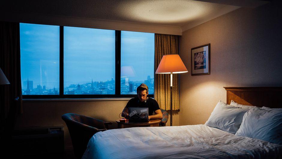 Ein Mann sitzt im Sessel am Laptop.