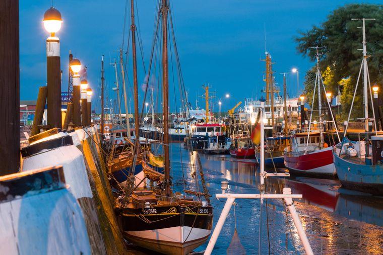 Boote liegen bei Ebbe im Museumshafen in Büsum in Schleswig-Holstein.